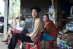 A man and his wife pose for photograph at their roadside coffee shop and store along Highway 1, north of Lang Co, Vietnam. Dec. 28, 2012.