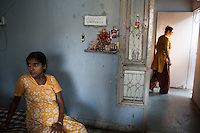 Dieties and gods from a variety of religions adorn the walls as surrogates laze around and chat with each other, as they spend the entire pregnancy, in the surrogate's house in Anand, Gujarat, India on 11th December 2012. Photo by Suzanne Lee / Marie-Claire France