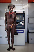 Asike Halu, 67, near a BRI bank ATM machine. Asike makes money from tourists, allowing them to take his picture and charging 5 to 10 thousand rupiahs (GBP 0.26 - 0.52) per shot. He also provides local guide services. Asike makes from 120,000 to 720,000Rupiah (GBP 6.34 - 38.08) a day and keeps his money in the BRI Bank.