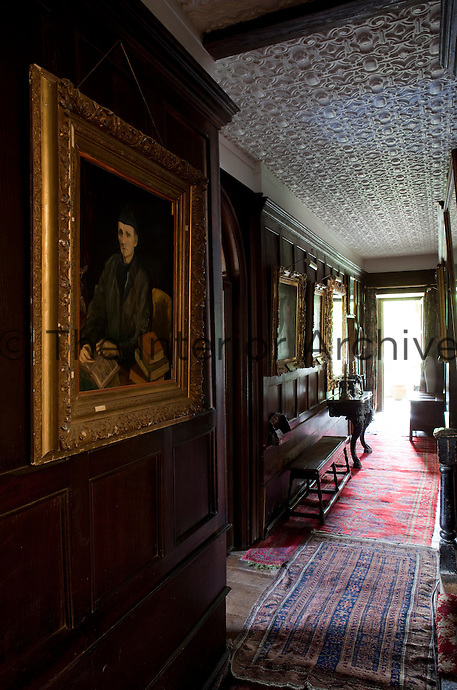 A dark oak-panelled corridor is lined with family portraits and features an elaborate plasterwork ceiling