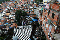 View from top of Favela Santa Marta - a house´ slab-cover ( laje ) used as recreational area painted with colors ( black and white ) and symbol ( lonely star ) of Botafogo Football Club, a famous Rio de Janeiro soccer team. Sometimes the residents manage to gain title to the land and then are able to improve their home. 4-pavements house at left, illegal construction. Since 2008 Santa Marta has a Pacifying Police Unit ( Unidade de Polícia Pacificadora, also translated as Police Pacification Unit ), abbreviated UPP, a law enforcement and social services program which aims at reclaiming territories, more commonly favelas, controlled by gangs of drug dealers.