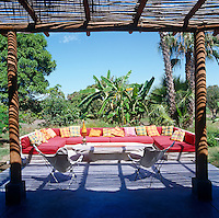 On the sun deck the red covers of the large banquette sofa are intensified by the vivid greens of the lush tropical garden