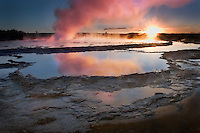 A setting sun snd warm evening light add to the drama of an eruption of Great Fountain Geyser in Yellowstone National Park