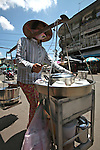 A woman carries a mobile kitchen in District 11 in Ho Chi Minh City, Vietnam. Thousands of women make a living cooking soup and other dishes on sidewalks throughout the city. Aug. 16, 2011.