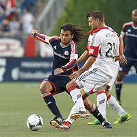 New England Revolution midfielder Juan Carlos Toja (7) takes on the defense. In a Major League Soccer (MLS) match, the New England Revolution (blue) tied D.C. United (white), 0-0, at Gillette Stadium on June 8, 2013.