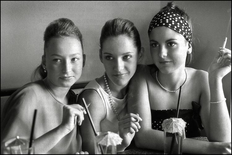 Three teenagers sitting together smoking