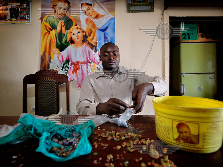 A coltan (columbite-tantalite) dealer in Goma. Coltan (fine black mineral, centre of picture) is used in consumer electronics products such as mobile phones, DVD players, and computers. It has been cited by many as being the main financial aid to the present-day conflict in the Congo.