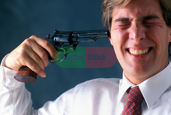 depressed man on the verge of committing suicide holding gun to his head