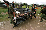 Soldiers carry the body of a dead FARC rebel that was killed in combat with government troops in Granada, about 180km outside of Bogota. (Photo/Scott Dalton)
