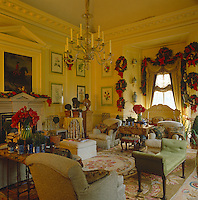 Vases of red Amaryllis echo the red in the garlands and wreaths which decorate the walls of this yellow drawing room