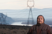 """Rex Buck Jr., leader of the Wanapum Indians is photographed on a hillside surrounded by power lines and the Columbia River behind him on February 3, 2011.   """"The river flows in us and we're a part of the river and we're also a part of this land.""""  said Buck. The Wanapum Indians never moved onto a reservation but negotiated peacefully with a power company to remain on their land.  The power company today is the Grant County Public Utility District.  (photo credit Karen Ducey)"""