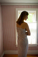 Woman standing in room in front of window