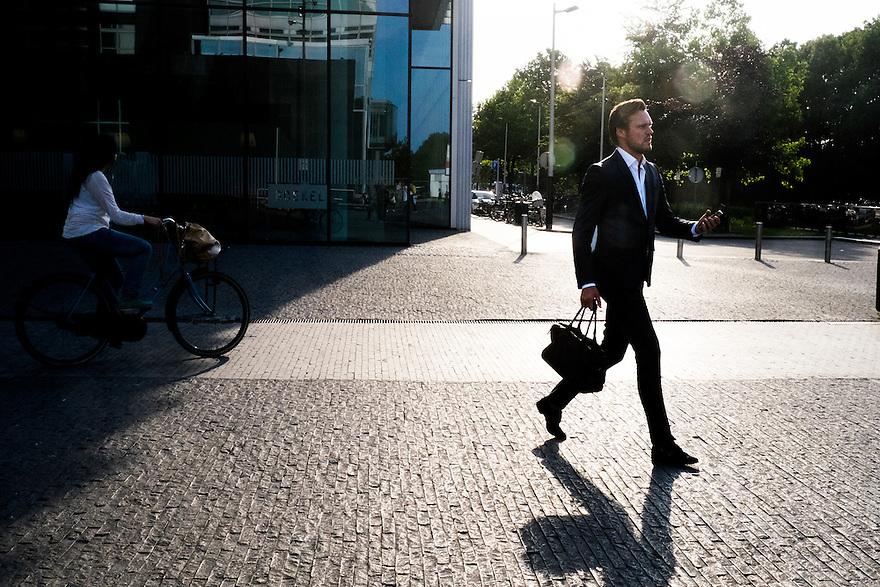 Nederland, Amsterdam, 16 juli 2015<br /> Amsterdam Zuidas. Kantoorpersoneel van de zuidas op weg naar het ns-station.<br /> <br /> Foto: Michiel Wijnbergh