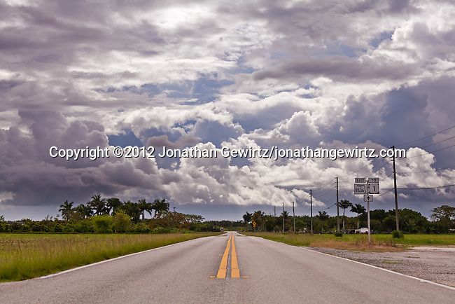 Ingraham Highway, Florida Route 9336, heads away from Everglades National Park and towards Homestead, Florida and a sky filled with dark rain clouds.