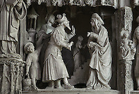 Anne and Joachim take Mary to the temple as promised, Mary willingly climbs the 15 steps. Joachim wears a hat with upturned points and a large collar, Anne wears a beaded cloak. The Presentation of Mary in the temple, by Jean Soulas, upper scene from the choir screen, 1519-25, Chartres Cathedral, Eure-et-Loir, France. These sculpted scenes show the change in style from Gothic to Renaissance in the early 16th century in France. Chartres cathedral was built 1194-1250 and is a fine example of Gothic architecture. It was declared a UNESCO World Heritage Site in 1979. Picture by Manuel Cohen