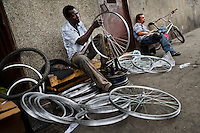 A bicycle mechanic works with a spoke wrench on bicycle wheel outside a small scale bicycle factory in Cali, Colombia, 27 June 2014. Due to the strong, vibrant cycling culture in Colombia, with cycling being one of the two most popular sports in the country, dozens of bike workshops and artisanal, often family-run bicycle factories were always spread out through the Colombian cities. However, growing import of cheap bicycles and components from China during the last decade has led to a significant decline in domestic bicycle production. Traditional no-name bike manufacturers are forced to close down their factories, struggling to survive in the competitive bicycle market.