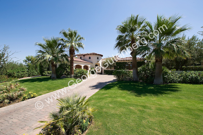 Lush landscaping surrounds elegant mediterranean style home