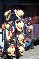 Tzutuhil Maya girl selling straw hats and weavings in Santiago Atitlan, Guatemala