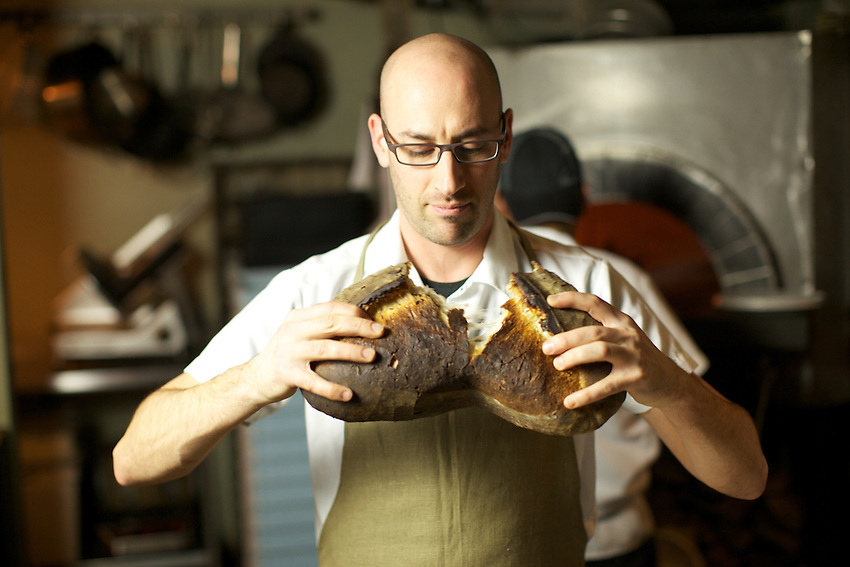 JERSEY CITY, NJ - FEBRUARY 12, 2014: Chef Dan Richer of Razza Pizza Artigianale cracking open a loaf of rustic bread. The bread is baked nightly in the restaurant's wood-burning pizza oven. CREDIT: Clay Williams for Edible Jersey.<br /> <br /> <br /> &copy; Clay Williams / http://claywilliamsphoto.com