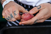 Close up on a chef's tatooed hands as he peels a red-skinned potato.
