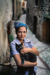 01003_11, Camino, Italy, 09/2004, ITALY-10012. A portrait of a woman with her black cat.<br />
