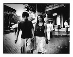 Young Mumbaikar woman, wearing a sleeveless blouse walks hand in hand with her partner in Colaba district of Mumbai, India.