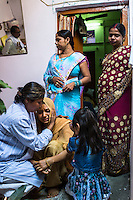 Santwana Manju of Guria (extreme left) comforts Sharda, 20, as she weeps, overwhelmed with emotion, during her pre-wedding ceremonies in her mother's (in blue) brothel where she grew up in the Mau Red Light area in Mau, Uttar Pradesh, India on 17 November 2013. Commercial Sex Worker's children growing up in the brothels are pampered and groomed to be the next generation of prostitutes, traffickers or pimps, however, Sharda is being married off into a community outside, sealing her future away from this vicious cycle.