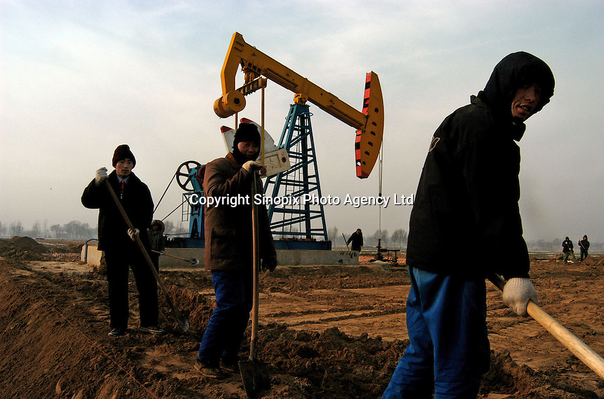 Workers at the Sinopec Petrochemical oil field in Puyang, Henan province, China. Farmers in the area often steal natural gas for cooking and heating. They steal the gas from the pipe-line filling a big plastic bag in an hour. As soon as one finishes filling a bag, another family will fill another bag, it goes on continuously. A bag of natural gas is enough fuel for up to one week...PHOTO BY HI SHE / SINOPIX