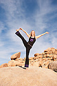 Woman in powerful joyful yoga pose outdoors.