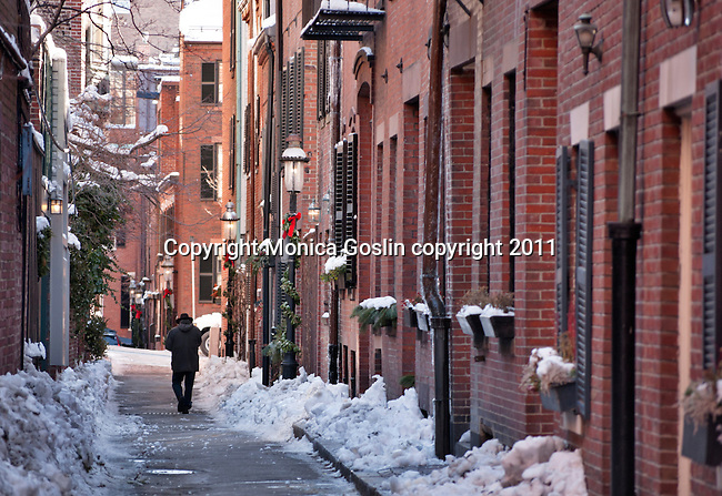 A snowy street in Beacon Hill with holiday decorations and wreaths in Boston, Massachusetts