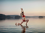 Young woman practicing Hatha yoga Low Lunge on a floating platform in water on the lake during misty sunrise in the morning. Yoga Anjaneyasana posture. Muskoka, Ontario, Canada.