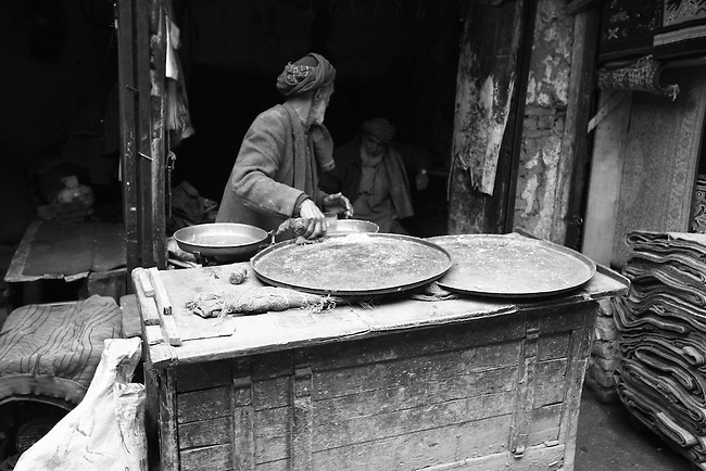 A merchant sifts rice on a pan outside a shop in the central market of Kabul, Afghanistan. Despite the ever-present mud and miserable winter weather, the market bustles daily with commerce of all kinds. Taliban attacks have so far been infrequent in the Afghan capital, and as life goes on at a normal pace, the war often seems far away.  Feb. 3, 2009.