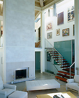In the living room of a house in San Francisco the massive chimney breast makes the most of the double-height ceiling and creates a stunning focal point