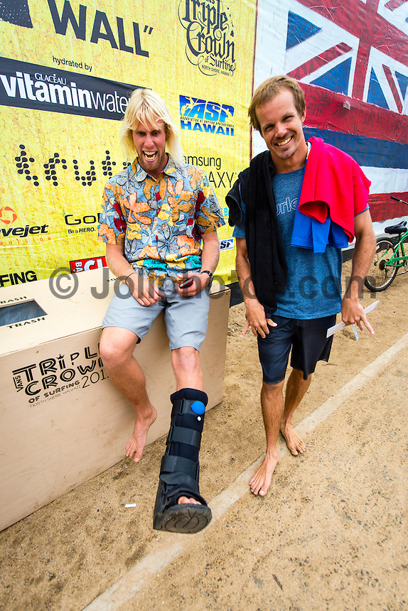North Shore, Oahu, Hawaii  - (Saturday, Nov. 30, 2013) Dane Gudauskas (USA) with torn tendons in his left ankle and wearing a moon boot with good friend Brian Toth (PRI)-- Eleven time world champion Kelly Slater rarely surfs in competition outside of elite ASP World Championship Tour events; it's a strategy for staying balanced in his life, competing at a consistently high level, and minimizing risk of injury and strain as he moves further into his 40s. So the opportunity to see him in action at the Vans World Cup of Surfing today - a Prime rated event - in a rare heat with Dane Reynolds (USA), Heitor Alves (Brazil), and Joan Duru (France), was good reason for a maximum crowd to fill Sunset Beach.The Vans World Cup of Surfing is the second event of the Vans Triple Crown of Surfing. Photo: joliphotos.com