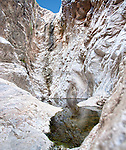 A pool sits beneath white rocks cliffs.