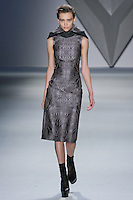 Mila Krasnoiarova walks runway in a steel vault jacquard sleeveless sheath dress with oversized detachable charcoal melton hood, from the Vera Wang Fall 2012 Vis-a-gris collection, during Mercedes-Benz Fashion Week Fall 2012 in New York.