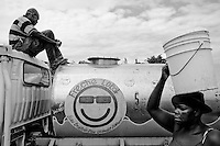 A woman carries a bucket past a truck delivering clean water to people living in a camp for those displaced by the recent earthquake in Petionville, outside Port-au-Prince, Haiti.