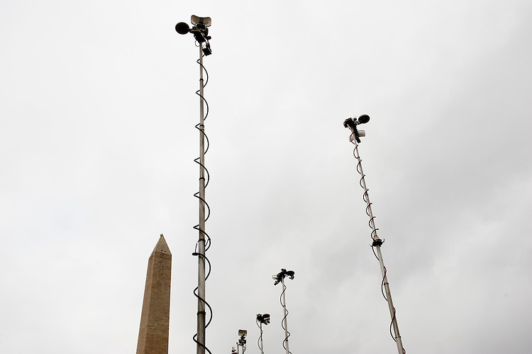 UNITED STATES - SEPTEMBER 27: Local and national television news trucks stand ready for live broadcasts at the base of the Washington Monument as a worker installs rigging at the top of the Washington Monument on Tuesday, Sept. 27, 2011, so that a team of rappelling engineers can inspect the landmark for damage caused by the 5.8 magnitude earthquake that hit the DC area in August. (Photo By Bill Clark/Roll Call)