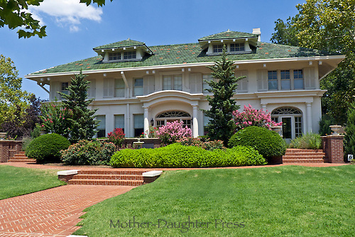 White Stucco house with green tile roof and blooming crepe myrtle flowers front view, Heritage hills, OKC, USA