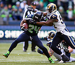 Seattle Seahawks running back Marshawn Lynch (24) is wrapped up  St. Louis Rams linebacker Alec Ogletree (52) at CenturyLink Field in Seattle, Washington on December 28, 2014.  The Seahawks officially wrapped up the No. 1 seed in the NFC playoffs shortly after beating the Rams, 20-6. Despite the Cowboys and Packers also winning to finish 12-4, the Seahawks (12-4) won the multi-team tiebreaker and earned home-field advantage throughout the playoffs for the second consecutive season.  ©2014. Jim Bryant Photo. All Rights Reserved.