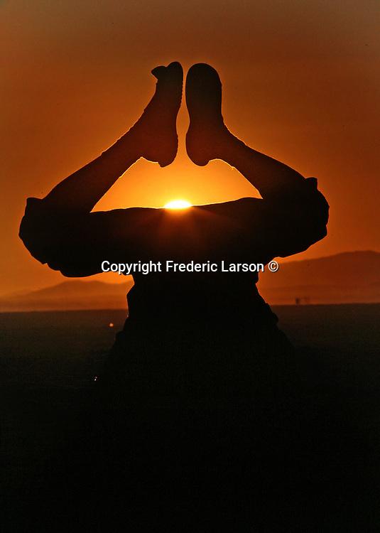 A man's legs frame the rising sun off the desert playa at Black Rock, Nevada.