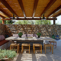 The dining terrace is shaded by a roof of chestnut thatch