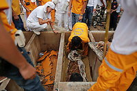 Unclaimed bodies are taken out of graves during a Thai Chinese ceremony at the Mang Teung Sua Jung Cemetery in Chonburi province southeast of Bangkok March 18, 2012. Every 10 years, hundreds of people wearing white, a customary colour for funerals and visiting temples, gather at this cemetery to exhume and cremate corpses as they believe they are helping the dead who have no friends or relatives. The ashes of the unclaimed bodies are spread on the sea to make room at the burial ground for more unclaimed bodies in the coming years. The tradition originated 90 years ago after diseases like Malaria killed many Thais of Chinese descent living in Chonburi.  REUTERS/Damir Sagolj (THAILAND)
