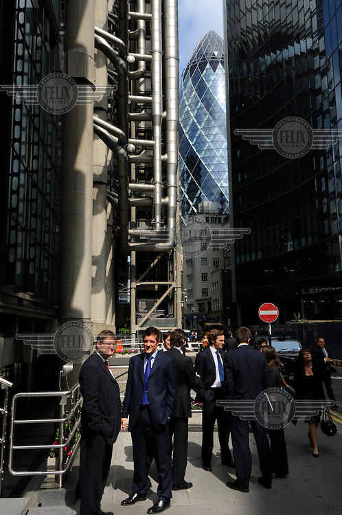 City of London workers at lunchtime on the street, with two of the districts iconic structures behind them - Lloyds Tower and the Swiss Re building, known colloquially as 'the Gherkin' and officially as 30 St Mary Axe.