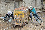 Miners move an ore cart outside a mine in Potosi, Bolivia. The mine produces silver and other metals.