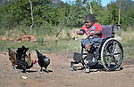 Peter Makura feeds chickens at his home in the village of Berejena, near Masvingo, Zimbabwe. Makura uses a wheelchair provided by the Jairos Jiri Association with support from CBM-US. Jairos Jiri also helped Makura start his income-generating poultry operation.