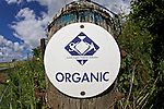 Oranic certifiaction sign on fence post entering field