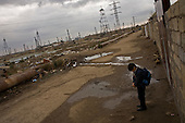 Baku, Azerbaijan .December 14, 2006..Just a few meters from the British Petroleum's massive multi-billion dollar off-shore platform being built on shore, is one of the poorest districts near Baku. Most of the residents are refugees from Nagorno-Karabakh region settled here during the war...A child make his way home after school in the shadows of the old rigs and the new BP construction sight.