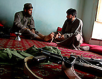 Two foot soldiers from the Wardak Mobile Patrol Unit discuss their next operation in the comfort of a safe haven property
