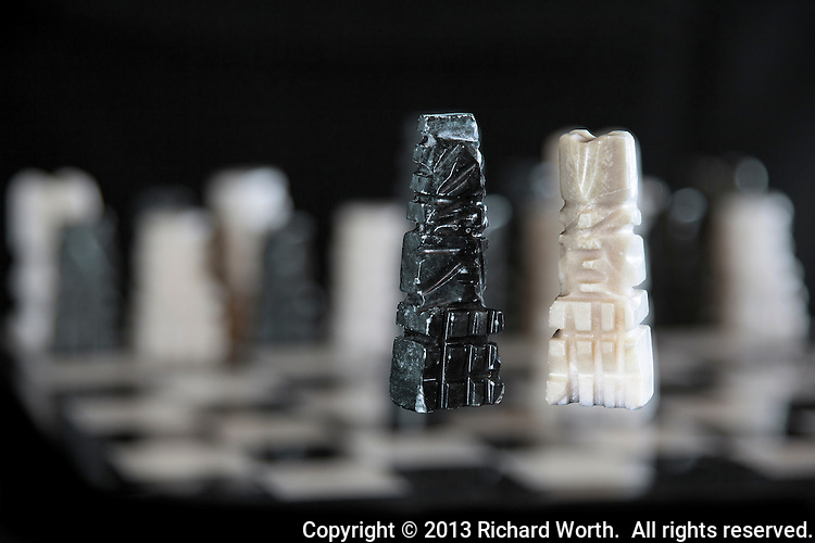 The opposing king and queen of an onyx chess set stand in sharp focus surrounded by other pieces and the black and white chess board in soft focus.